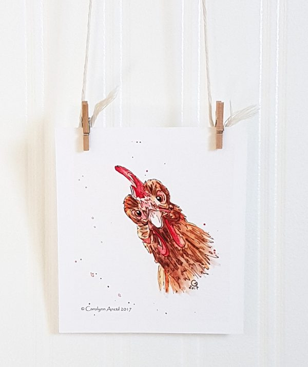 Chicken Portrait mini watercolour illustration hangs suspended by 2 miniature clothespins against a white background. The face of a chicken faces forward at an angle to the left.