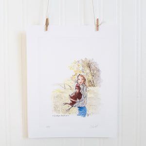 Country Kid watercolour illustration hangs suspended by 2 miniature clothespins against a white background. A young girl stands in the foreground in the country. She's wearing a long sleeved, striped shirt in blue, yellow & white and blue jeans. She faces left, with her head turned to face the viewer and holds a large brown chicken in her arms.