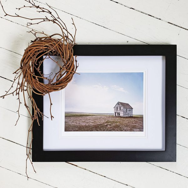 Photo of Prairie Farmhouse photograph in a black frame against a whitewashed wood background. A wreath of willow wood sits on the top left corner of the frame.