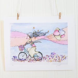 Joy Ride watercolour illustration hangs suspended by 2 miniature clothespins against a white background. A young woman rides a blue bicycle with a basket of flowers on the handlebars. Her black hair is tied with a green ribbon and streams out behind her. Stars float around her hair. She's facing left and holds the string to five multi-coloured, heart shaped balloons in her right hand. She's blowing a bubblegum bubble and wearing layered sweaters in green, purple, and pink. Her skirt is green and she's barefoot. She rides the bike through heart shaped flowers and a landscape of blue, pink and orange flowing colours.
