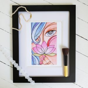 Photo of Lady with Lotus watercolour illustration in a black frame against whitewashed wood background. A string of pearls lays on the top left corner. A daisy chain cut from white paper lays across the bottom left corner and a make up brush sits inside the right side of the frame.