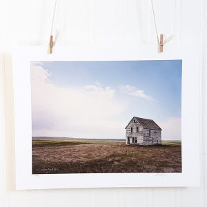 Prairie Farmhouse photograph hangs suspended by 2 miniature clothespins against a white background. An abandoned farmhouse sits on a flat prairie landscape to the right of the frame.