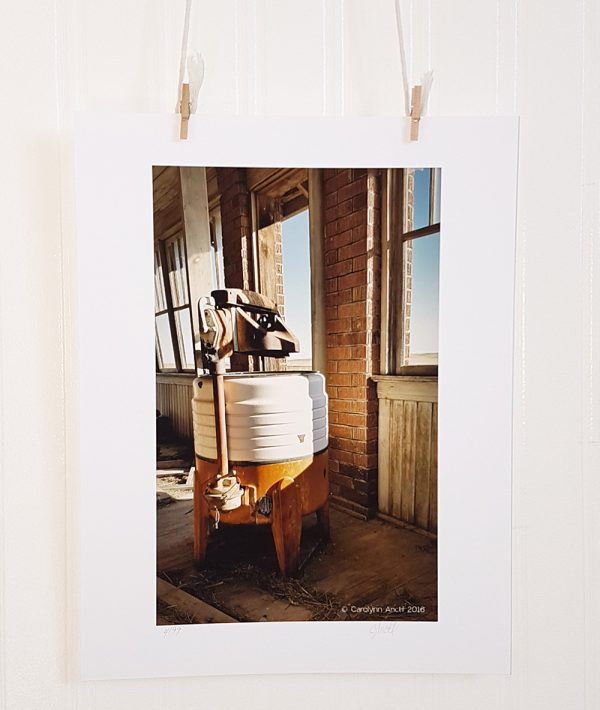 Wash Day photograph hangs suspended by 2 miniature clothespins against a white background. An antique wringer washing machine in white and orange sits on the porch of an abandoned farmhouse.