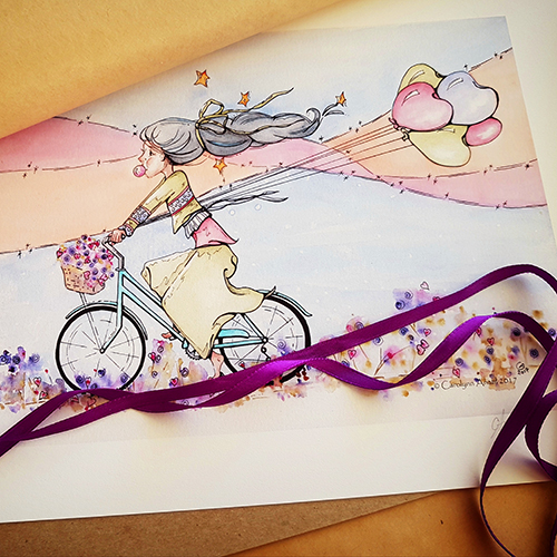 Joy Ride watercolour Illustration pictured with brown kraft wrapping paper and purple ribbon. A young woman rides a blue bicycle with a basket of flowers on the handlebars. Her black hair is tied with a green ribbon and streams out behind her. Stars float around her hair. She's facing left and holds the string to five multi-coloured, heart shaped balloons in her right hand. She's blowing a bubblegum bubble and wearing layered sweaters in green, purple, and pink. Her skirt is green and she's barefoot. She rides the bike through heart shaped flowers and a landscape of blue, pink and orange flowing colours.