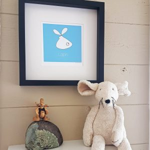 Photo of blue Lapin/Bunny watercolour illustration in black frame and hung on a taupe wall. A rock with a ceramic figurine sit on a white shelf below the print. A white stuffed mouse sits on the shelf to the right of the print.