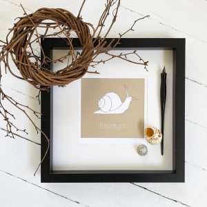 Photo of taupe Escargot watercolour illustration in black frame. A wreath of willow wood sits on the top left of the frame .Seashells and a black fountain pen sit inside the right of the frame. All against a whitewashed wood background.