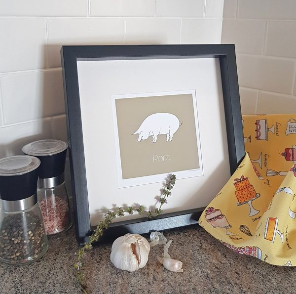 Photo of taupe Porc/Pig watercolour illustration. in black frame and set on kitchen counter with white subway tile backsplash. A set of salt & pepper shakers sit to the left of the frame. A sprig of thyme and a garlic bulb sit in the foreground. Yellow fabric patterned with baked goods appears to the right of the frame.