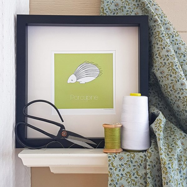 Photo of green Porcupine watercolour illustration in black frame set atop a white shelf. Antique scissors lean against the bottom left of the frame. 2 spools of thread in white and green sit in the foreground to the right of the frame and green fabric patterned with bees is draped along the right side of the frame.