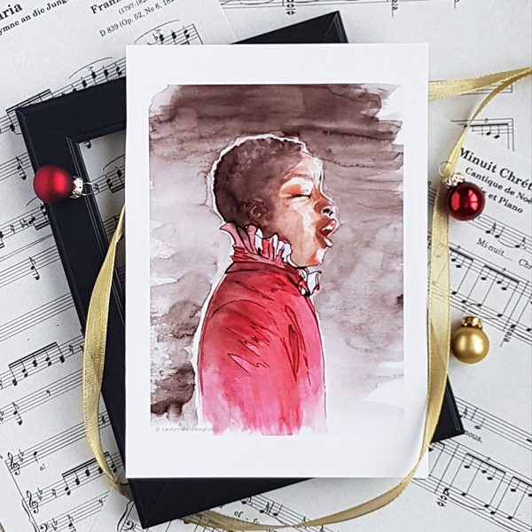 Photo of Choirboy watercolour illustration. Print sits atop an empty black frame which sits atop sheets of music. Gold ribbon winds through the frame. 2 miniature red Christmas balls and one gold one sit in the frame.