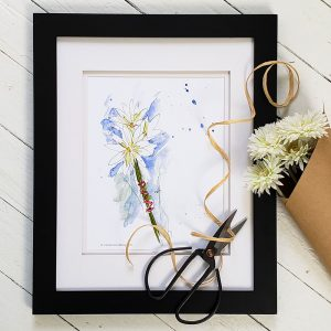Photo of Daisy Nosegay watercolour illustration in a black frame against a whitewashed wood background. An antique pair of scissors are placed on the bottom right corner of the frame. Raffia twine wraps through the blades of the scissors and up to a bouquet of daisies wrapped in brown kraft paper to the right of the frame.