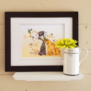 Queen Bee Watercolour Illustration Remarque in Black Frame set on a white shelf. Small milk jug holds a lime green flower in the right foreground.