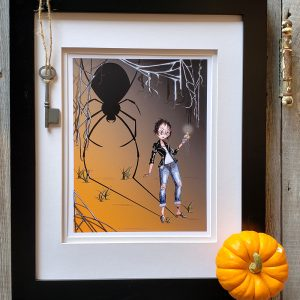 Framed Black Widow print against a weathered wood background. Miniature pumpkin in the bottom right corner and skeleton key in upper left corner.
