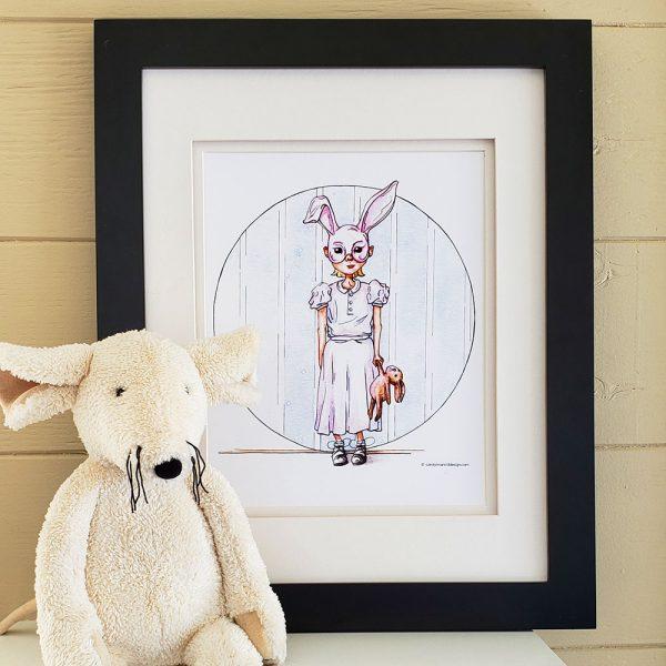 Rabbit Rabbit Print in black frame with stuffed animal.