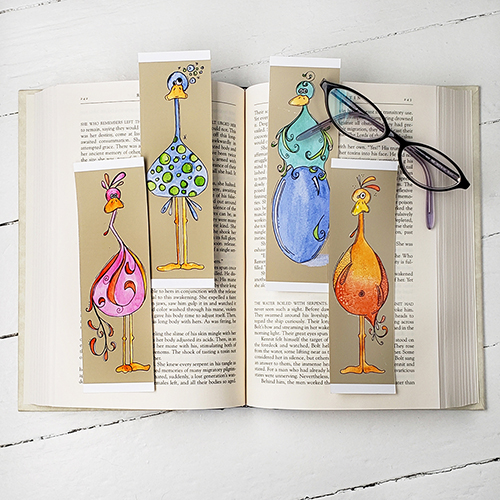 Four Goofy Bird bookmarks set against an open book, with a set of reading glasses.