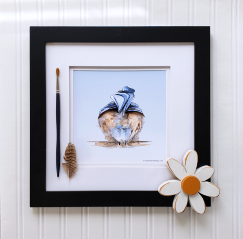 Fluffy Butt Print in a black frame with a feather, paintbrush & daisy decoration.