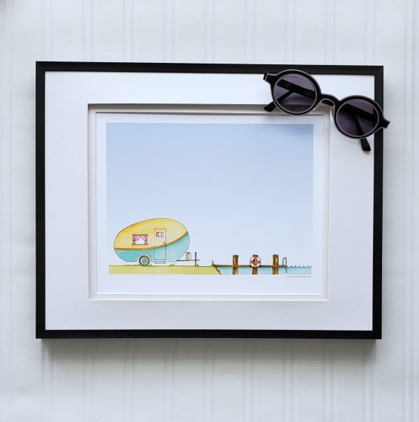 Lakeside Caravan print in a frame pictured with sunglasses